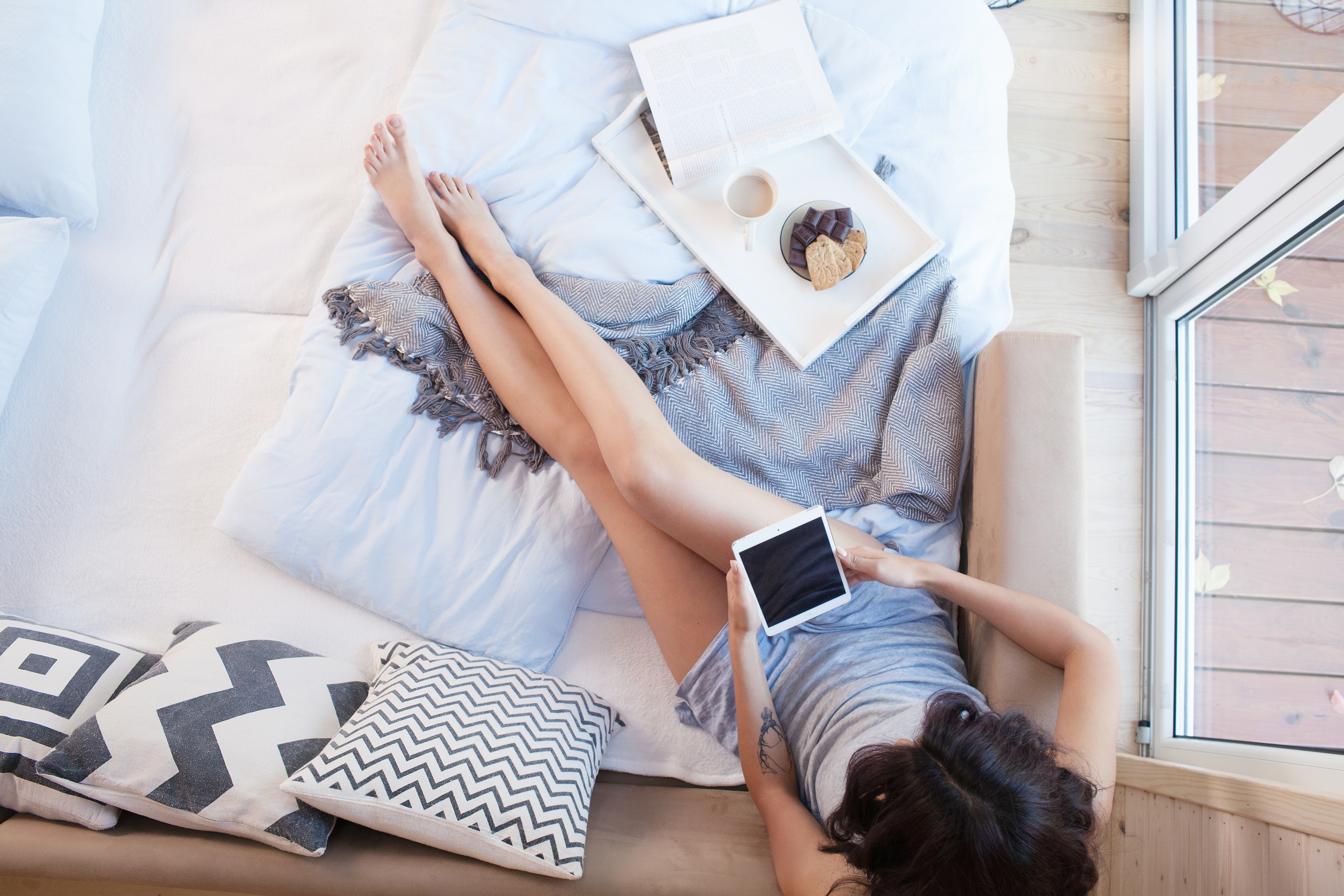 Young beautiful brunette woman with tablet computer sitting down on the bed by the window. Top view from above. Lazy day off concept